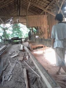Pekerja Bansau lagi memotong kayu glondongan menjadi papan dengan ukuran tertentu dengan menggunakan mesin pemotong
